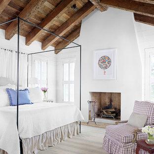 Lantlig inredning av ett sovrum, med vita väggar och en standard öppen spis