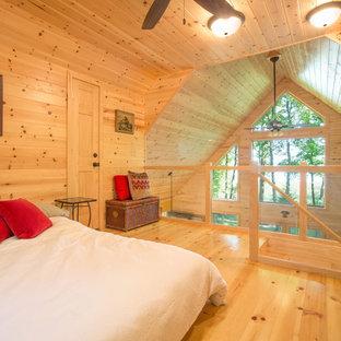 Exemple d'une chambre mansardée ou avec mezzanine montagne avec un sol en bois brun.
