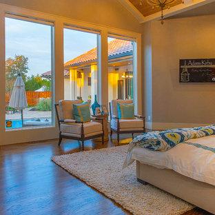 Modelo de dormitorio principal, tradicional renovado, grande, con paredes grises, suelo de madera en tonos medios, chimenea de doble cara y marco de chimenea de baldosas y/o azulejos