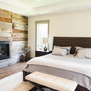 Foto de dormitorio principal, rural, grande, con paredes beige, suelo de madera oscura, chimenea de doble cara, marco de chimenea de madera y suelo marrón