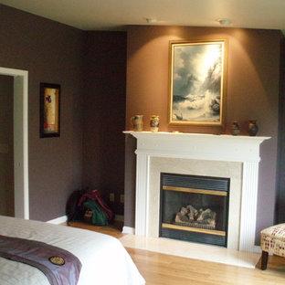 На фото: хозяйская спальня в стиле современная классика с фиолетовыми стенами, полом из бамбука, стандартным камином и фасадом камина из дерева с