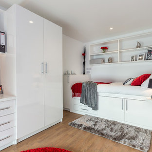 This is an example of a contemporary bedroom in Dorset with white walls and medium hardwood floors.