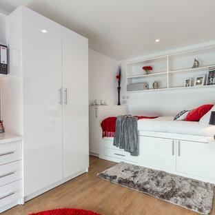 Bild på ett funkis sovrum, med vita väggar och mellanmörkt trägolv