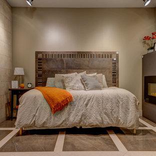 Diseño de dormitorio principal, contemporáneo, de tamaño medio, con paredes beige, marco de chimenea de piedra, suelo de mármol, chimenea lineal y suelo marrón