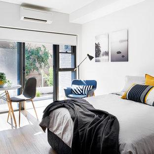 Immagine di una piccola camera da letto design con pareti bianche e pavimento in vinile