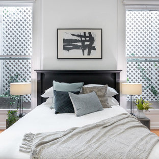 Inspiration for a scandinavian bedroom in Sydney with white walls, medium hardwood floors and brown floor.