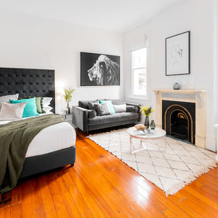 This is an example of a scandinavian bedroom in Sydney with white walls, medium hardwood floors, a standard fireplace and brown floor.