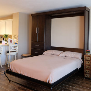 This is an example of a mid-sized modern loft-style bedroom in Philadelphia with beige walls, porcelain floors and brown floor.