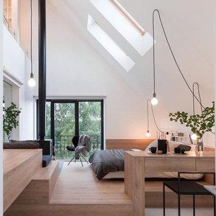 На фото: спальня в скандинавском стиле с белыми стенами, светлым паркетным полом и печью-буржуйкой с