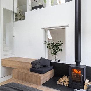 Diseño de dormitorio nórdico, pequeño, con paredes blancas, suelo de madera clara y estufa de leña