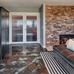 На фото: гостевые спальни среднего размера в стиле модернизм с синими стенами, бетонным полом, стандартным камином и фасадом камина из кирпича