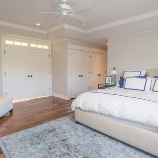Esempio di una grande camera matrimoniale american style con pareti grigie, pavimento in legno massello medio, camino classico e cornice del camino in legno