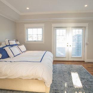 Modelo de dormitorio principal, de estilo americano, grande, con paredes grises, suelo de madera en tonos medios, chimenea tradicional y marco de chimenea de madera