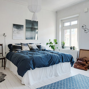 This is an example of a large scandinavian master bedroom in Gothenburg with white walls, painted wood flooring and no fireplace.