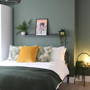 Ispirazione per una camera degli ospiti minimalista di medie dimensioni con pareti verdi, pavimento in laminato, nessun camino e pavimento marrone