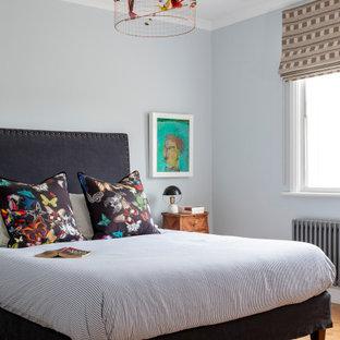 Bohemian bedroom in London with grey walls, medium hardwood flooring and brown floors.