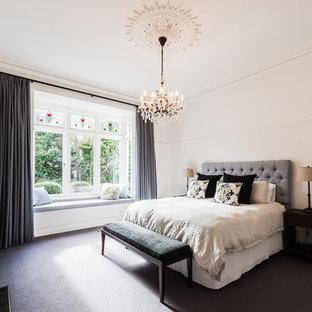 Ejemplo de dormitorio principal, contemporáneo, grande, con paredes blancas, moqueta, chimenea tradicional, marco de chimenea de madera y suelo gris