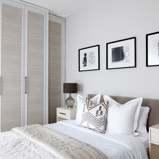Inspiration for a mid-sized transitional master laminate floor and beige floor bedroom remodel in London with beige walls