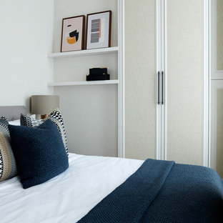 Design ideas for a small traditional guest bedroom in London with beige walls, laminate floors, no fireplace and beige floors.