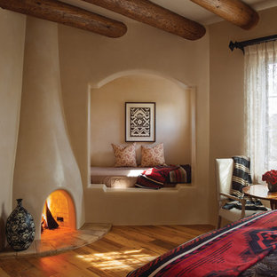 Foto på ett amerikanskt gästrum, med beige väggar, mellanmörkt trägolv, en spiselkrans i gips och en standard öppen spis