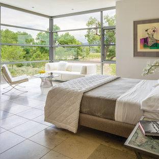 Modelo de dormitorio contemporáneo, grande, con suelo de travertino y paredes beige