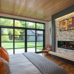 Immagine di una grande camera matrimoniale moderna con pareti bianche, pavimento in legno massello medio, camino lineare Ribbon, cornice del camino in pietra e pavimento marrone
