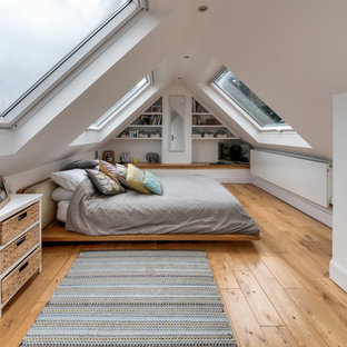 Photo of a large contemporary guest bedroom in London with white walls, medium hardwood flooring and brown floors.
