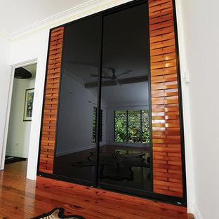Ejemplo de dormitorio tipo loft, exótico, sin chimenea, con paredes blancas y suelo de madera en tonos medios