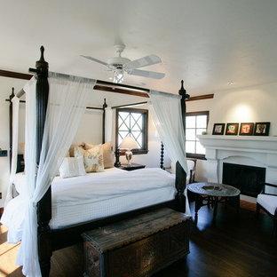 Стильный дизайн: большая хозяйская спальня с белыми стенами, темным паркетным полом, стандартным камином и фасадом камина из штукатурки - последний тренд