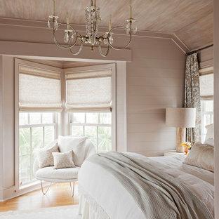 Immagine di una camera matrimoniale costiera con pareti beige e pavimento in legno massello medio