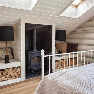 Lantlig inredning av ett sovrum, med en öppen vedspis och ljust trägolv