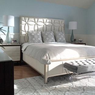 Modelo de dormitorio principal, clásico renovado, extra grande, con paredes azules, suelo de madera en tonos medios, chimenea tradicional y marco de chimenea de madera