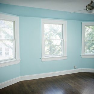 This is an example of a mid-sized traditional guest bedroom in New York with blue walls, dark hardwood floors and no fireplace.