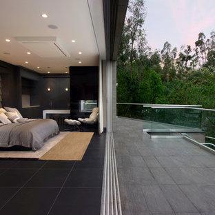 Diseño de habitación de invitados actual, de tamaño medio, con paredes grises, suelo de mármol, chimenea de doble cara, marco de chimenea de piedra y suelo negro