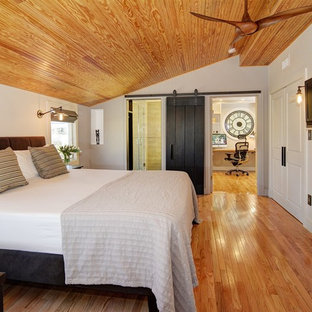 Modelo de dormitorio principal, clásico renovado, extra grande, con paredes grises y suelo de madera en tonos medios