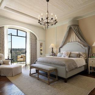 Aménagement d'une chambre adulte méditerranéenne avec un mur beige, un sol en bois foncé et un sol marron.