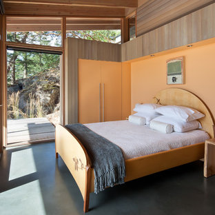 シアトルのコンテンポラリースタイルのおしゃれな主寝室 (コンクリートの床、オレンジの壁、青い床)