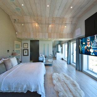 Cette image montre une grande chambre parentale design avec un mur beige et un sol en bois clair.