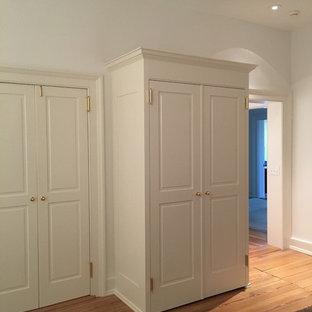 Ejemplo de habitación de invitados tradicional, de tamaño medio, con paredes grises, suelo de madera clara, chimenea tradicional, marco de chimenea de ladrillo y suelo naranja