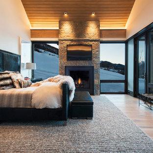デンバーの巨大なコンテンポラリースタイルのおしゃれな主寝室 (淡色無垢フローリング、標準型暖炉、石材の暖炉まわり、ベージュの壁、茶色い床) のレイアウト