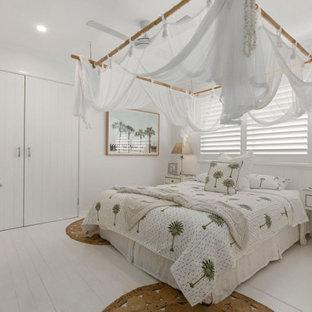 На фото: гостевая спальня в морском стиле с белыми стенами, деревянным полом и белым полом с