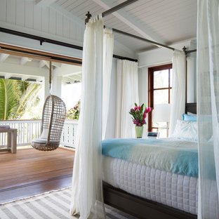 Inspiration for a tropical bedroom in Orange County with white walls, dark hardwood floors and brown floor.