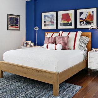 Imagen de dormitorio marinero, de tamaño medio, sin chimenea, con suelo de madera en tonos medios, paredes azules y suelo naranja