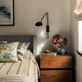 Example of a mid-century modern medium tone wood floor and brown floor bedroom design in Seattle with white walls