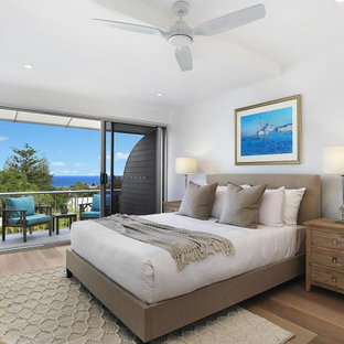 Large mediterranean master bedroom in Sunshine Coast with white walls, medium hardwood floors and brown floor.