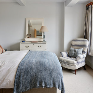 Small coastal guest bedroom in Surrey with white walls, carpet and beige floors.