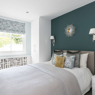 Example of a mid-sized zen carpeted and beige floor bedroom design in London with blue walls