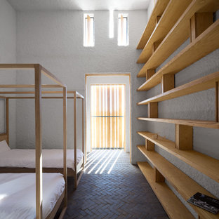 Design ideas for a contemporary guest bedroom in Other with white walls and brick floors.