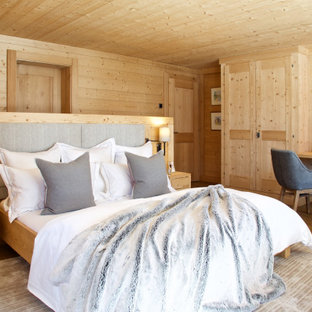 Design ideas for a large rustic master bedroom in London with beige walls, medium hardwood flooring and brown floors.