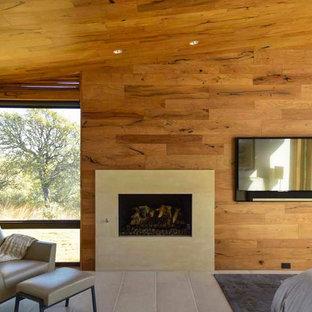 Foto de dormitorio principal, contemporáneo, de tamaño medio, con suelo de piedra caliza, chimenea tradicional, marco de chimenea de piedra y suelo beige